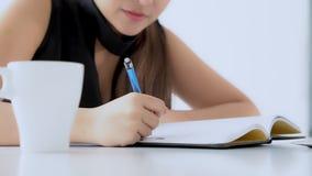 Nahaufnahmefrau, die in der Wohnzimmerstudie sitzt und Notizbuch und Tagebuch zu Hause schreibend lernt stock video