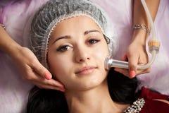 Nahaufnahmefrau, die elektrisches ultrusound Gesichtsmassage am Schönheitssalon empfängt lizenzfreie stockfotos