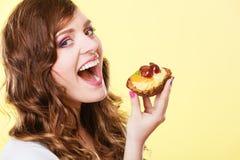 Nahaufnahmefrau, die Fruchtkuchen-Bonbonlebensmittel isst Stockfoto