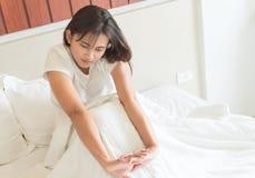 Nahaufnahmefrau, die Hand auf ihrem Bett nachdem dem Aufwecken im MOR ausdehnt stockfotos