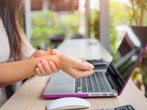 Nahaufnahmefrau, die ihre Handgelenkschmerz von der Anwendung des Computers hält Stockfoto