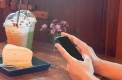 Nahaufnahmefrau, die Smartphone in der Kaffeestube verwendet Lizenzfreie Stockbilder