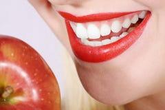 Nahaufnahmefrau mit den weißen Zähnen und Apfel Lizenzfreies Stockbild