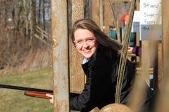 Nahaufnahmefrau mit Gewehr an der Wurfscheibenschießenstrecke Stockbild
