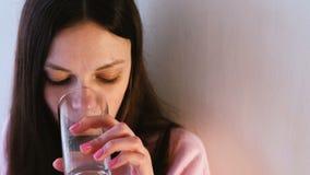 Nahaufnahmefrau ` s Gesicht, das ein Wasser vom Glas trinkt stock footage