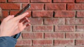 Nahaufnahmefrau ` s Hände grast Internet-Seiten am Handy, der im Winterpark sitzt stock video footage