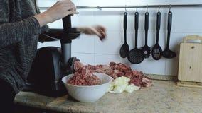Nahaufnahmefrauen ` s übergibt Rindfleisch und Schweinefleisch und Zwiebel durch Fleischwolf zu Hause hindurchführen Seiten-wiev stock footage