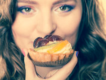Nahaufnahmefrauengesicht und Fruchtkuchen Lizenzfreies Stockfoto