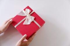 Nahaufnahmefrauenhände, die rote Geschenkbox mit weißem Band auf weißem Hintergrund senden stockfoto