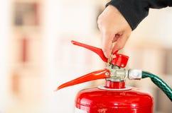 Nahaufnahmefrauenhände mit roter nailpolish Vertretung, wie man Feuerlöscher betreibt Stockbilder