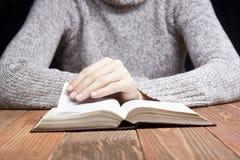 Nahaufnahmefrauenhand, die Taschenbuch hält, um zu lesen Stockfotografie