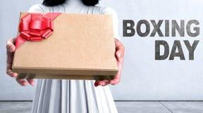 Nahaufnahmefrauenhand mit Geschenkbox und 26. Dezember-Mitteilung Lizenzfreie Stockbilder