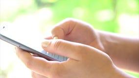 Nahaufnahmefrauenhand unter Verwendung Touch Screen Telefons im Park stock video