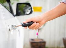 Nahaufnahmefrauenhand, welche die Fernsteuerungsautoalarmsysteme hält Lizenzfreies Stockfoto