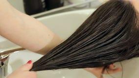 Nahaufnahmefriseur spritzt auf sch?tzendem ?l des nass Haarm?dchens Junges asiatisches M?dchen, das Haar mit dem Finger getrennt  stock video