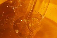 Nahaufnahmegefangennahme eines Wasserspritzens auf einer gelben Schüssel Lizenzfreies Stockfoto