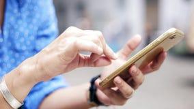 Nahaufnahmegesamtlänge von den weiblichen Händen, die Smartphone und Grasenwebsite halten stock footage