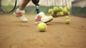 Nahaufnahmegesamtlänge von weiblichen Beinen in den Sportturnschuhen und -prothese auf ihrem Bein, das Tennisbälle vom Tennis auf