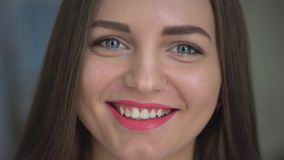 Nahaufnahmegesicht der schönen jungen Frau, die an der Kamera lächelt 4 k-Porträt des attraktiven jungen lächelnden Mädchen-Schau stock footage