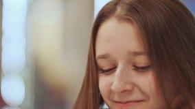 Nahaufnahmegesicht des jungen schönen Schulmädchens, trinkender Kaffee von einer Schale stock video footage