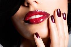 Nahaufnahmegesicht einer Frau mit den schönen sexy roten Lippen und dunklem Na Lizenzfreie Stockfotografie