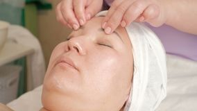Nahaufnahmegesichtsmassage eines asiatischen Mädchens in einem Schönheitssalon Die Hände eines Cosmetologist das Verfahren von Ha stock video footage