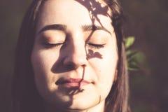 Nahaufnahmegesichtsporträt der jungen Frau im Wald lizenzfreie stockfotografie