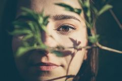 Nahaufnahmegesichtsporträt der jungen Frau im Wald lizenzfreie stockfotos