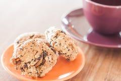 Nahaufnahmegetreideplätzchen auf orange Platte und Kaffeetasse Stockfotografie