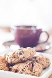 Nahaufnahmegetreideplätzchen mit violetter Kaffeetasse Stockfotografie