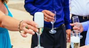Nahaufnahmehände der Braut und des Bräutigams mit Glaschampagner Stockbild