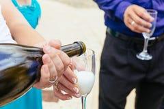 Nahaufnahmehände der Braut und des Bräutigams mit Glaschampagner Lizenzfreies Stockbild