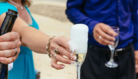 Nahaufnahmehände der Braut und des Bräutigams mit Glaschampagner Lizenzfreie Stockfotografie