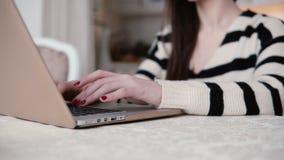 Nahaufnahmehände der jungen Frau benutzt Laptop in einem hellen Speisen Lizenzfreies Stockbild
