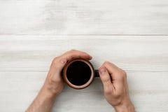 Nahaufnahmehände des Mannes einen Schalenkaffee halten Stockbilder