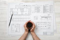 Nahaufnahmehände des Mannes Schalenkaffee über Zeichnungsplan in der Draufsicht halten Stockbilder