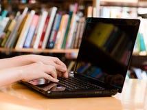 Nahaufnahmehände, die auf Notizbuch in der Bibliothek schreiben lizenzfreie stockbilder