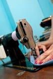 Nahaufnahmehände und altes Metallnähmaschine Lizenzfreies Stockfoto