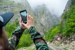 Nahaufnahmehände unter Verwendung des beweglichen nehmenden Fotobergblicks des Telefons auf Morgen Stockbild