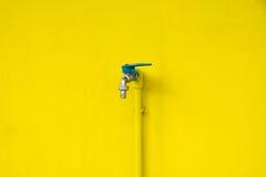 Nahaufnahmehahn auf konkretem gelbem Wandhintergrund Wasserlecken Lizenzfreie Stockbilder