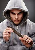 Nahaufnahmehaltung eines gefährlichen Gangsters Stockfotografie