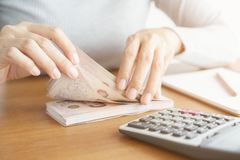 Nahaufnahmehand der asiatischen Frau, die den z?hlenden Taschenrechner und Geld z?hlen im Haus verwendet lizenzfreie stockbilder