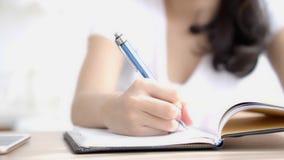 Nahaufnahmehand der asiatischen Frau sitzend in der Wohnzimmerstudie und lernend, Notizbuch und Tagebuch auf Tabelle zu Hause sch stock video footage