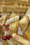 Nahaufnahmehand der goldenen Statue von Kinara bei Wat Phra Kaew in Bangkok, Thailand Stockfoto