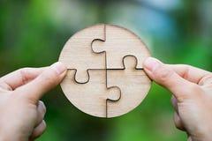 Nahaufnahmehand der Verbindung des Puzzlen, um den Auftrag abzuschließen stockfotos