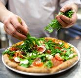 Nahaufnahmehand des Chefbäckers in der weißen einheitlichen Herstellungspizza an der Küche Lizenzfreies Stockbild