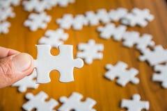 Nahaufnahmehand des Mannes Puzzlen der Teile mit halten, stockfotografie