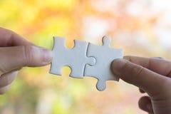 Nahaufnahmehand des Mannes Puzzlen mit Sonnenlichteffekt anschließend lizenzfreies stockfoto