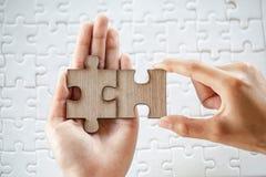 Nahaufnahmehand des Mannes Puzzlen mit Sonnenlichteffekt, Geschäftslösungen, Erfolg und Strategiekonzept anschließend lizenzfreie stockbilder