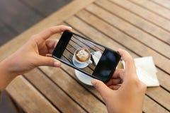 Nahaufnahmehand, die beweglichen nehmenden Fotokaffee des Telefons auf Tabelle hält Stockbild